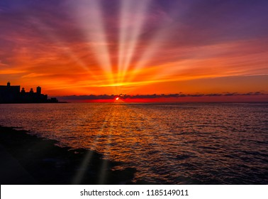 Sunset over Malecon and Atlantic Ocean with visible sun rays - Havana, Cuba