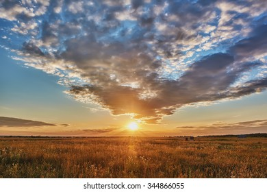 Sunset over meadows, field with clouds on blue sky