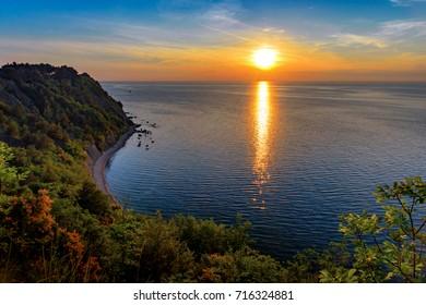 Sunset over Mesecev zaliv (Moon Bay), Strunjan, Slovenia. Moon Bay near Strunjan is probably the most beautiful stretch of the short Slovenian coastline. - Shutterstock ID 716324881