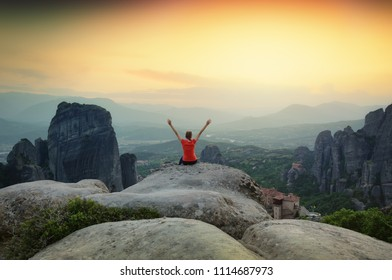 Sunset over Meteora monasteries in Greece. Girl tourist sitting on top of the rock and enjoying beautiful panoramic landscape of Meteora area