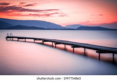Sunset over the mountain lake pier. Sunset lake pier. Lake pier at sunset. Mountain lake pier at sunset