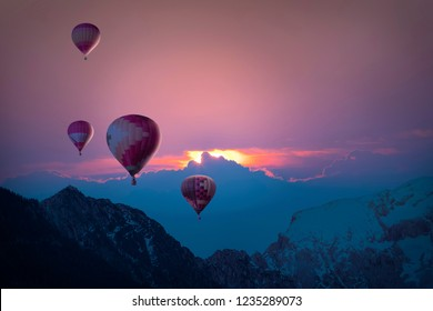 sunset over the mountains with hot air ballons