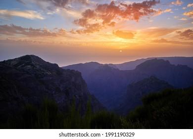 Sunset over mountains of Madeira Island. Colorful blue sky background, range dramatic clouds, aerial photography. Pico do Arieiro, Madeira Island, Portugal.