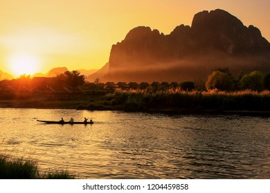 Sunset over Nam Song River with silhouetted rock formations and a boat in Vang Vieng, Laos. Vang Vieng is a popular destination for adventure tourism in a limestone karst landscape.