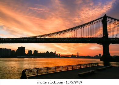 Sunset over New York City, filming on the south side of the Brooklyn Bridge, Brooklyn Bridge in the frame, water surface, embankment.Photos from my month tour of America