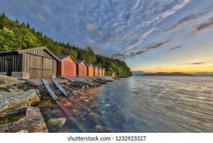 Sunset over Norwegian fjord with Colorful Boathouses near Rodven in More og Romsdal province at sunset