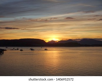 Sunset over Oban Bay looking to the Isle  of Mull in Scotland with several sailing boats