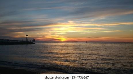 Sunset over the ocean with a jetty visible.  Photo taken in Menemsha on Martha's Vineyard, Massachusetts.