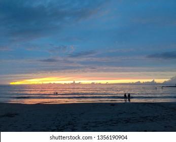 Sunset over ocean of KaunaÊ»oa (Mauna Kea) Beach in the foreground on the Kohala Coast on the Big Island Hawaii.