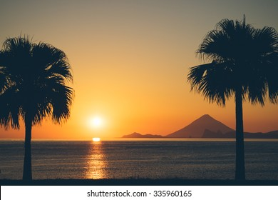 Sunset over ocean with palm trees and volcanic mountain, Mt. Kaimon, Kagoshima, Kyushu, Japan