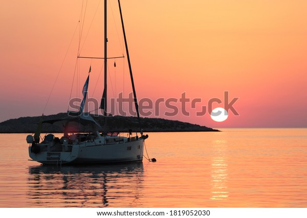 Sunset over the ocean with a silhouette of a sailboat moored to a mooring ball in front and a small island in the background