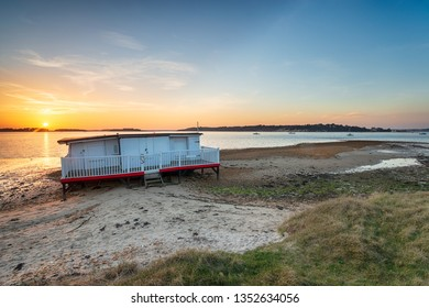 Sunset over an old houseboat on the beach at Bramble Bush bay on Studland on the Purbeck coast of Dorset