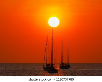 sunset over pole of yatch sailboat without vessel  parking on deep sea with colorful twilight evening sky background seascape.