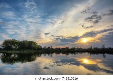 Sunset over pond. Silhouettes coast with houses and trees reflected in water.