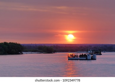 Sunset over a pontoon boat on the Zambezi River near Livingstone, Zambia