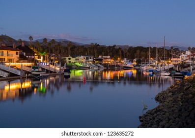 Sunset over residential development by water in Ventura California with modern homes and yachts boats