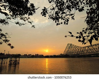 Sunset over river ganges with silhouette of leaves in the background.