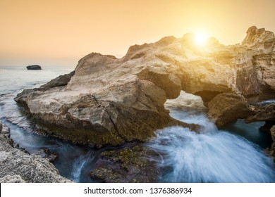 Sunset over rocky coast near Tropea in Calabria, Italy