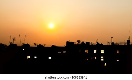 Sunset over rooftops with building lights