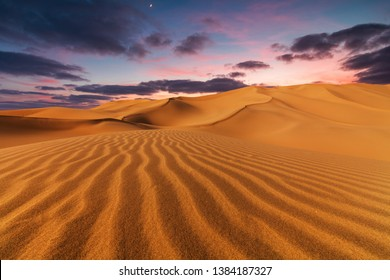 Sunset over the sand dunes in the desert.