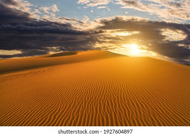 Sunset over the sand dunes in the desert. Arid landscape of the Sahara desert