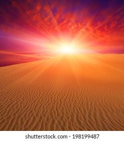 Sunset over sand dunes in desert