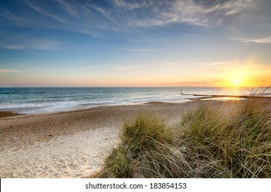 Sunset over sand dunes at Hengistbury Head beach near Bournemouth in Dorset