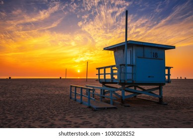 Sunset over Santa Monica beach with lifeguard observation tower in the foreground in Los Angeles, California