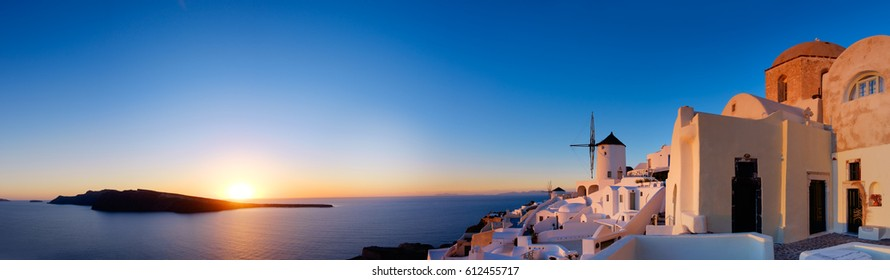 Sunset over Santorini island in Greece. Traditional church, apartments and windmills in Oia village on a sunset, panoramic image. Sky is classic blue, year of the 2020.