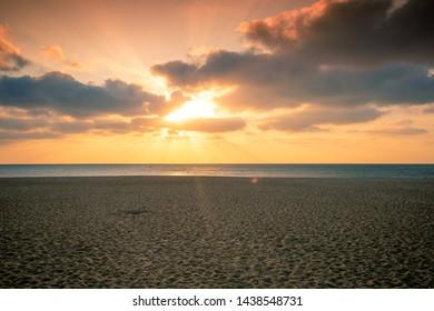 Sunset over the sea. Atlantic ocean in evening, beautiful nature, sandy beach
