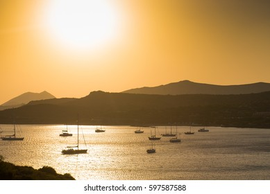 Sunset over the sea. Sunset over the bay with ships. Blur, light mist over the water
