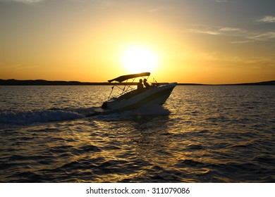 Sunset over the sea with a boat in the foreground. Menorca, Spain.