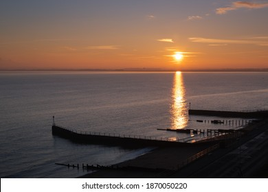 Sunset over the sea with a golden reflection of the sun reaching wooden groynes on a beach.