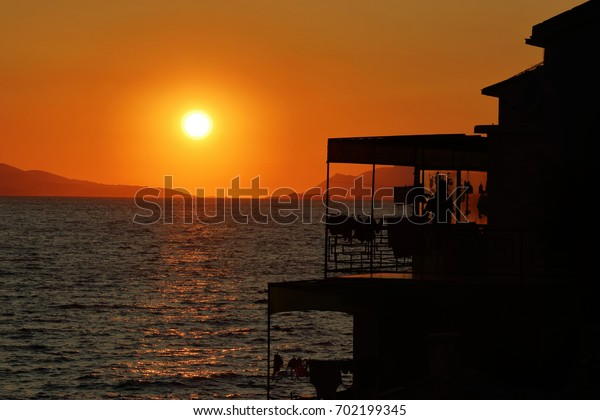 Sunset over the sea with house