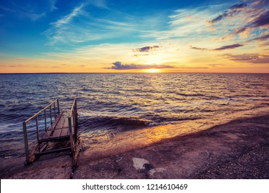 Sunset over sea, pier on the sea