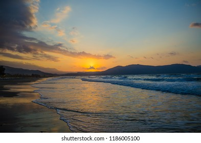 Sunset over the sea, the rolling calm waves, sandy beach. Skay orange-blue  light cloud.