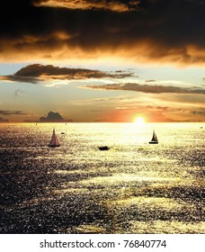Sunset over the sea with sailing boats