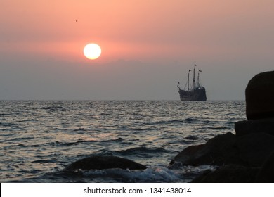 Sunset over sea with a tall ship