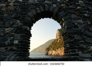 sunset over sea through window of old ruins
