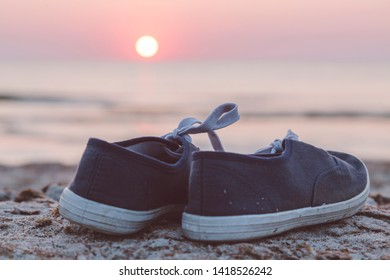 sunset over the sea, two sneakers at the beach