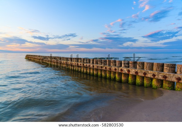 Sunset over sea with wooden breakwaters in foreground on Leba beach, Baltic Sea, Poland