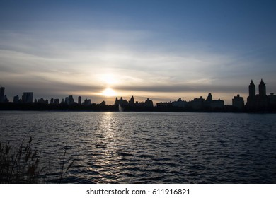 Sunset over silhouette buildings and lake with blue sky