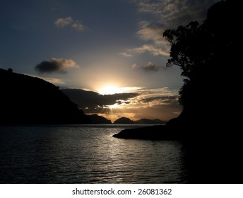 Sunset over silhouetted coastline, islands, trees and ocean.  Great Barrier Island, New Zealand