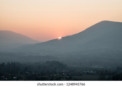 sunset Over Skalka hill with colorful sky, Radhost hill on the left side and part of Malenovice village bellow from new view point on Borova hill in Moravskoslezske Beskydy mountains in Czech republic