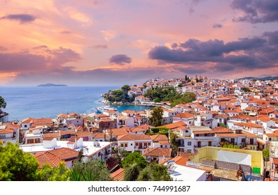 Sunset over Skiathos town on Skiatos Island, Greece. Beautiful view of the old town with boats in the harbour.
