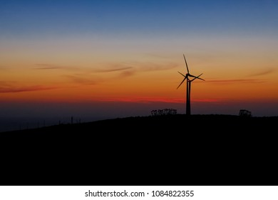 sunset over some wind turbine generator