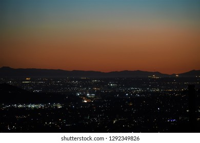 Sunset over Southern California with ships and city lights visible across Orange County, Long Beach and Catalina Island.