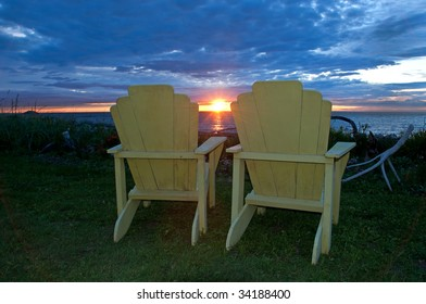 sunset over the St. Lawrence river seen between two adirondack (muskoka) chairs