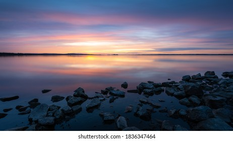 sunset over Steinhude lake as longexposure picture with stones in foreground