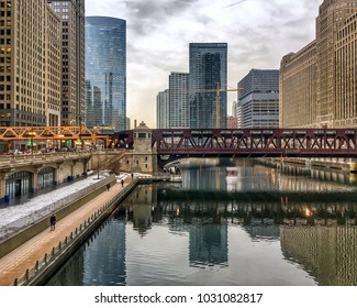 Sunset over a still, nearly frozen Chicago River, which is reflecting a replica of surrounding cityscape on its mirror-like surface.